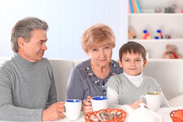 Мальчик пьет горячий шоколад и счастливые бабушка и дедушка