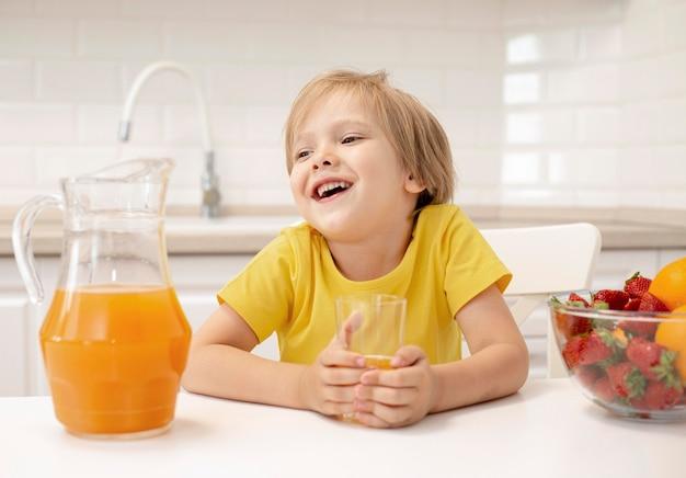 Мальчик пьет сок дома