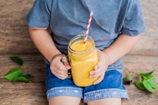 Мальчик пьет сочный коктейль из манго в стеклянной банке каменщика с полосатой красной соломой на старых деревянных фоне