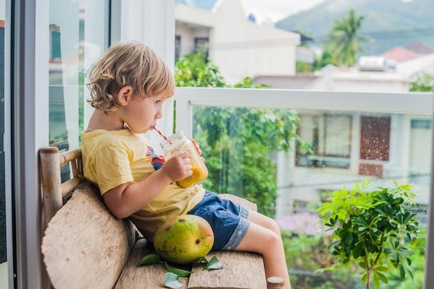 Мальчик пьет сочный коктейль из манго в стеклянной банке с полосатой красной соломкой