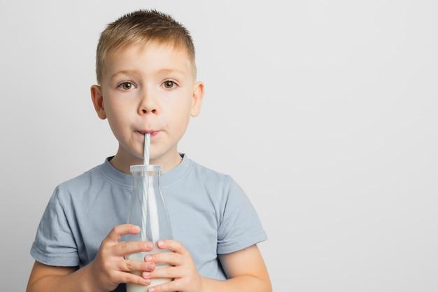 Мальчик пьет молоко в бутылке с соломой