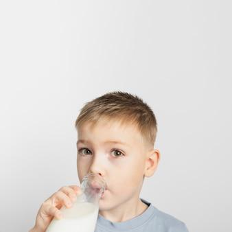 Мальчик пьет молоко из бутылки