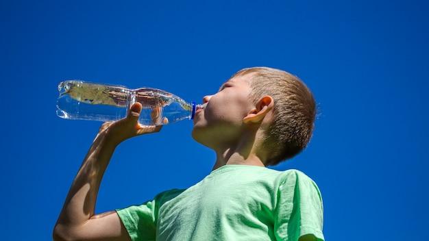 Мальчик пьет чистую прозрачную воду из пластиковой бутылки на фоне голубого неба