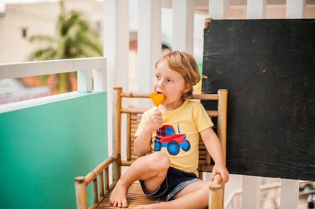スムージーパパイヤを飲む少年。健康食品のコンセプトです。テキスト用のスペースと黒い木の板