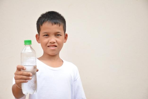 Boy drinking watercement gray background