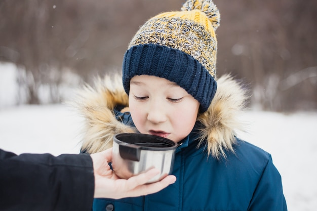 A boy drinks from a thermos of tea or a drink , winter walking, hiking, winter, winter clothing