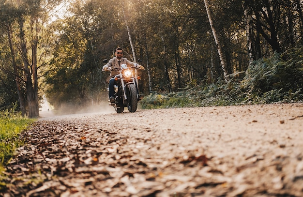 A boy drive a motorbike on stone road