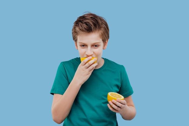Мальчик ест лимон, кислый вкус, гримасничать, эмоции на лице отрицательные,