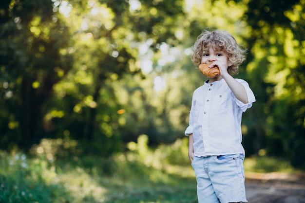 Boy eating croissant in park