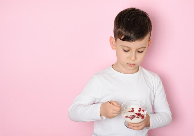 ピンクのスタジオの表面に白いtシャツでスグリとデザートヨーグルトを食べる少年