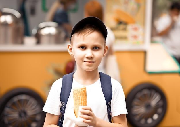 ストリートマーケットのフードトラックで新鮮なゆでトウモロコシを食べる少年。