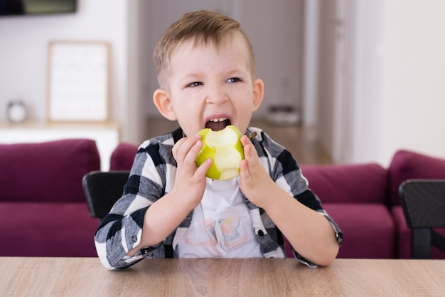 Мальчик ест зеленое яблоко за столом в гостиной.