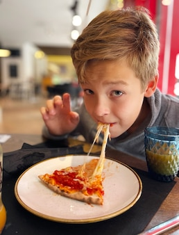 Boy eating pizza in a cafe. child likes melted cheese and enjoying tasty lunch