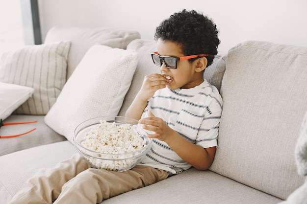 Boy eating popcorn.  boy africans in a glass. watching a children's movie.