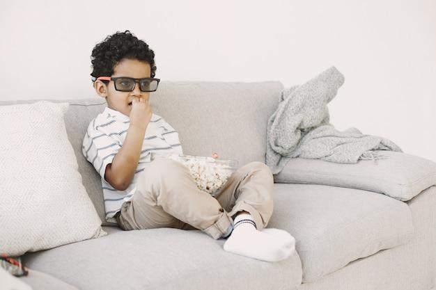 ポップコーンを食べる少年。ガラスの少年アフリカ人。子供向けの映画を見ています。