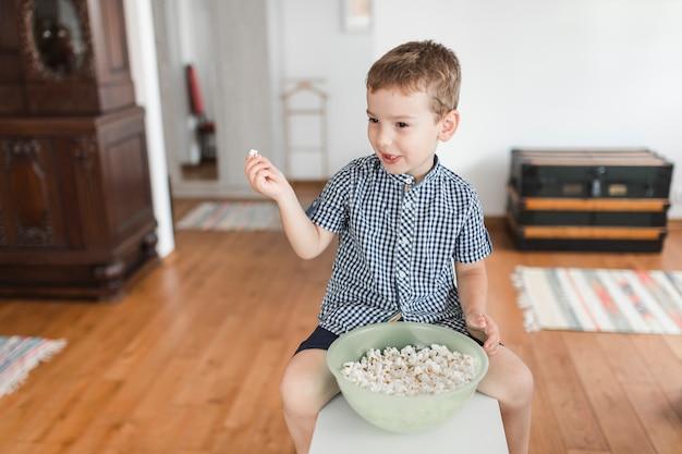 Boy eating popcorn at home