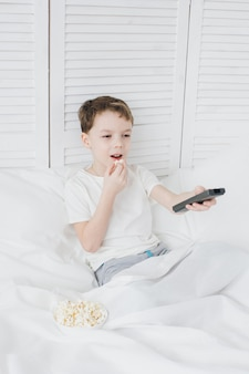 Boy eating popcorn sitting in bed and watching tv