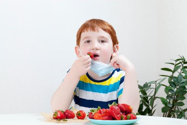 잘 익은 딸기를 먹는 소년
