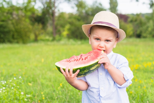 Boy eating slice of watermelon in the park