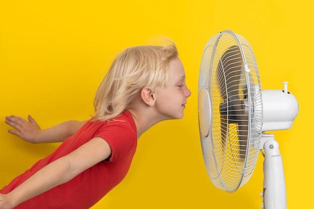 시원한 공기를 즐기는 소년. 노란색 표면에 아이와 팬. 실내 온도 조절.