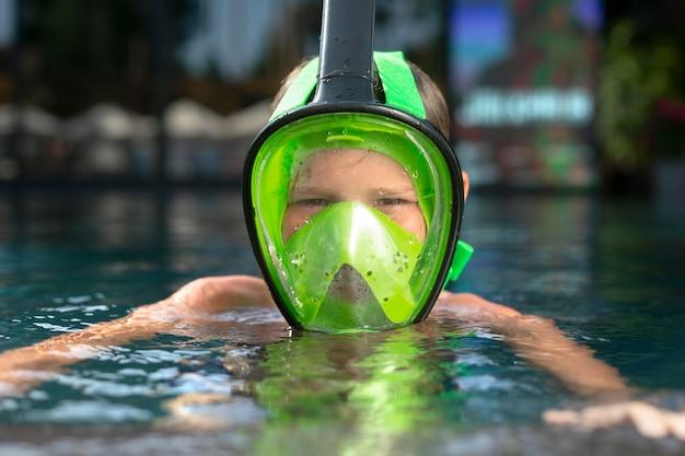 Мальчик наслаждается своим днем в бассейне с маской для подводного плавания
