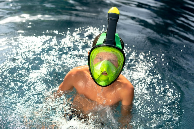 Boy enjoying his day at the swimming pool with scuba mask