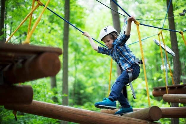 Boy enjoys climbing in the ropes course adventure
