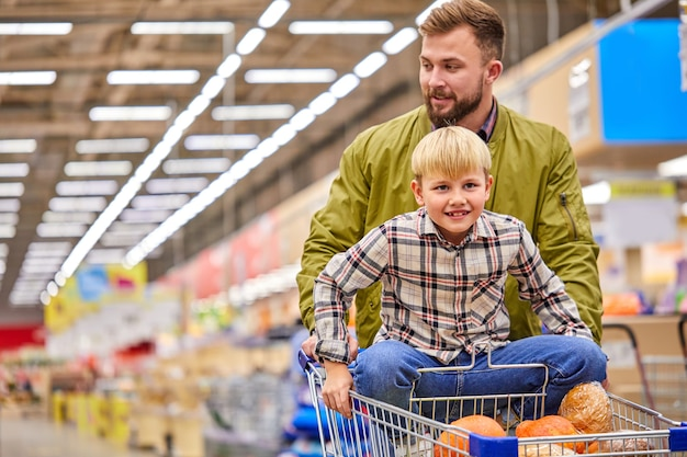 Мальчик любит делать покупки с отцом в супермаркете, красивый парень везет сына на тележке, веселится