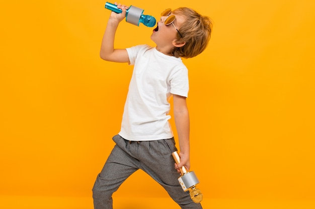 Boy enjoys singing into a microphone on an orange wall
