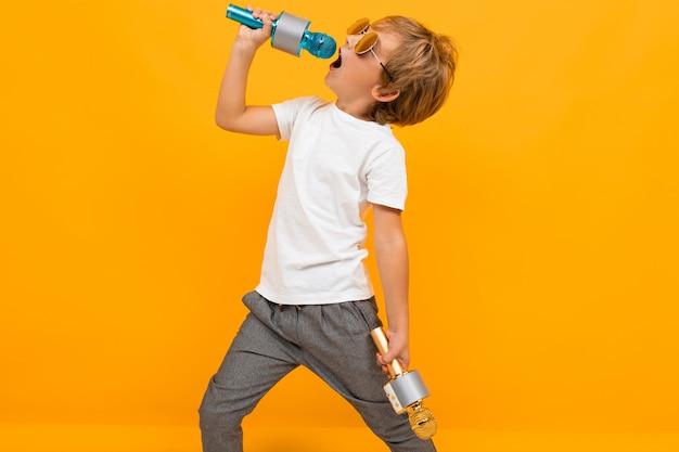 Boy enjoys singing into a microphone on an orange wall