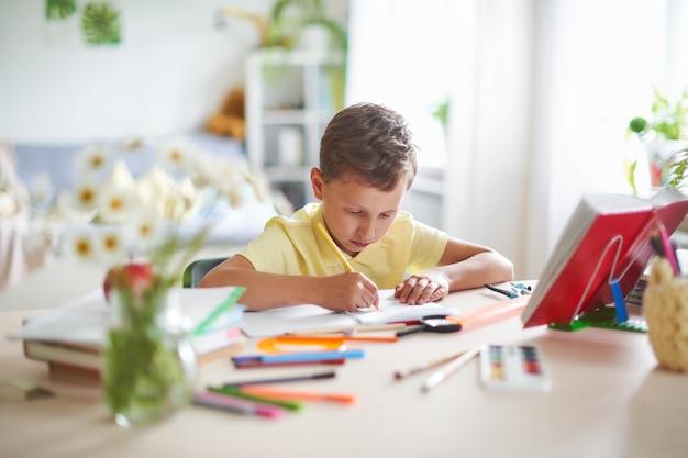 熱心にテーブルで書いたり描いたりする少年