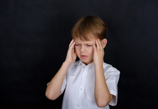Мальчик европейской внешности держится за голову от боли. концепция головной боли. изолировать на черном