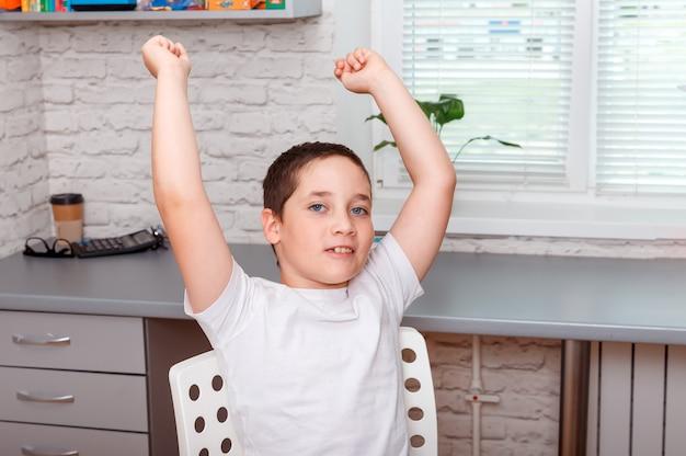 소년은 승리의 제스처를 표현하고 승리의 승리를 축하합니다.