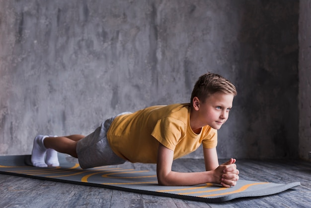 Boy exercising on exercise mat in front of concrete wall