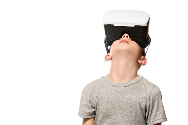 Мальчик испытывает виртуальную реальность, поднимая голову. изолировать на белом фоне. концепция технологии.