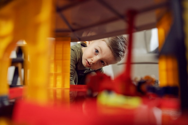 The boy explores while playing. a picture of a baby boy playing with toys indoors. a happy childhood in kindergarten, child development. kids education in daycare, playing a game and growing up