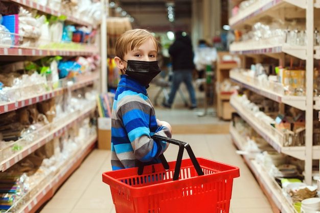 Boy in face mask in public crowded place. kid with shopping basket in supermarket. shopping with kid during coronavirus outbreak.