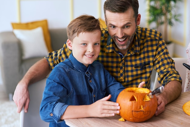 Boy and father carving pumpkin