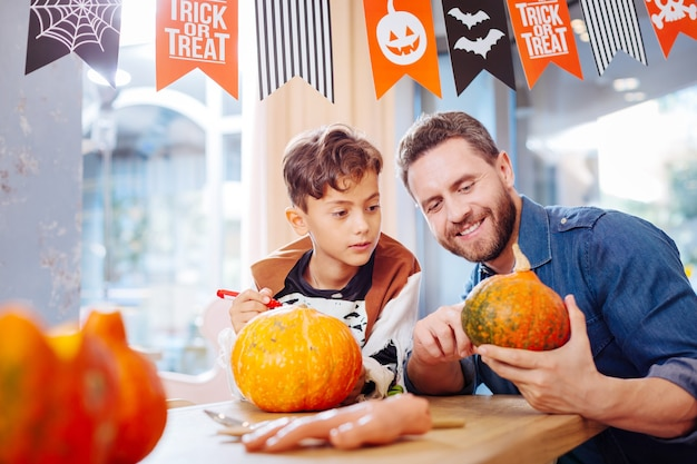 Boy and father. dark-haired handsome cute boy wearing skeleton costume watching his father carving pumpkin