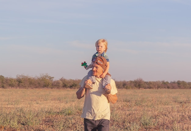 Boy on father shoulders with toy airplane. dad and son spend time outdoors