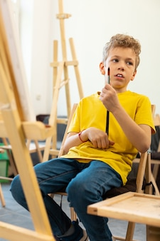 Boy feeling bored during the art lesson at school