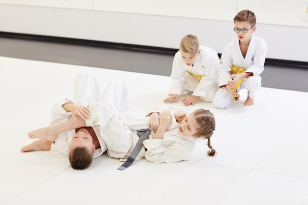 Мальчик борется с девочкой на уроке каратэ