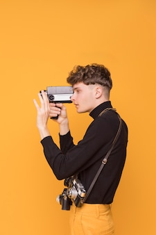 Boy filming with a camcorder in a yellow scene