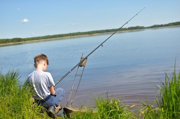 Boy fisherman on the shore of the lake with a fishing rod