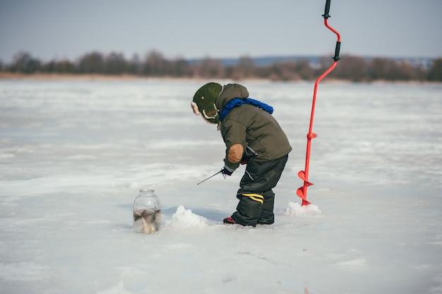 冬に釣りをする少年。かわいい男の子は冬の湖で魚を捕まえます。冬。屋外