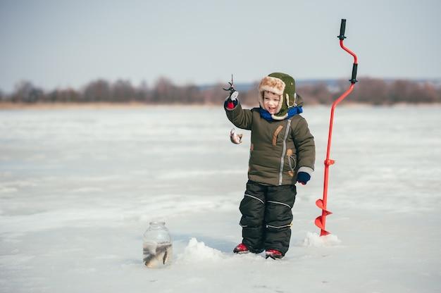 Мальчик, ловящий рыбу зимой. милый мальчик ловит рыбу в зимнем озере. зима. открытый
