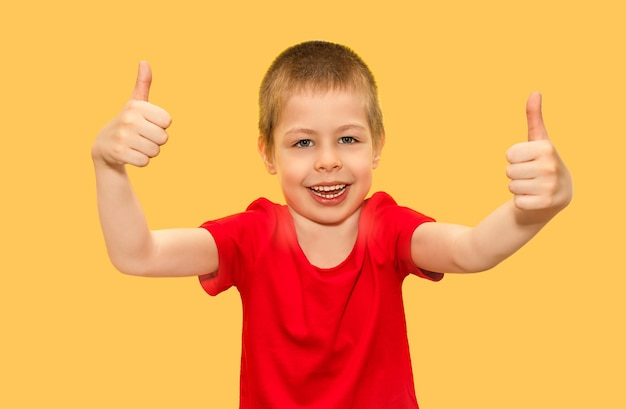 A boy fiveyearold child very cheerful smiling emotionally and showing a thumbs up