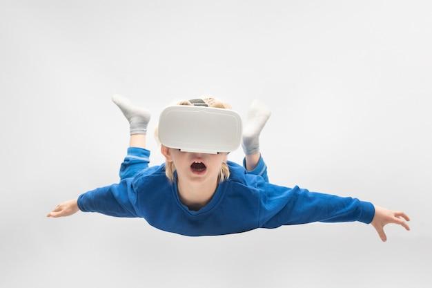 Boy flies in virtual reality glasses. white surface. virtual reality games.