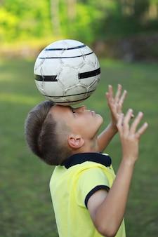 黄色いtシャツを着た少年サッカー選手が頭にボールを持ってサッカー場に立っています。