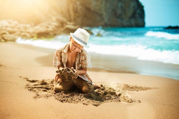 Boy found a turtle on the beach